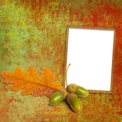 Old grunge frame with autumn oak leaves and acorns on the abstra