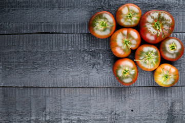 Tomatoes on the old wooden background