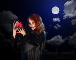 Witch with red potion on night sky background