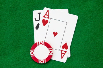 Blackjack hand with casino chip on green casino table
