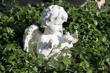 Engel mit Taube zwischen Grünpflanzen auf einem Grab