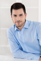 Business Mann in Hemd blau sitzend im Büro