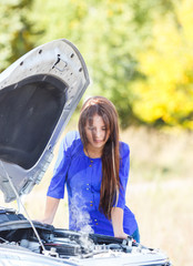 sad young girl with a broken vehicles