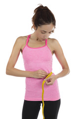 Fit woman measuring her waistline with a tape