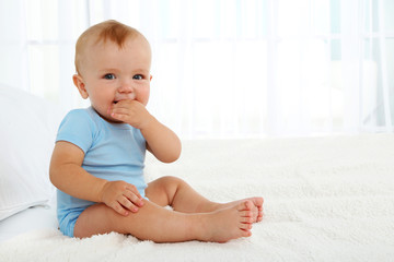 Cute baby boy on bed in room