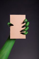 Green monster hand with black nails holding blank piece of cardb