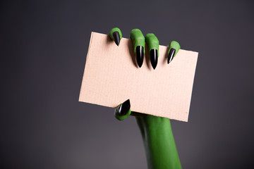 Green monster hand with sharp nails holding blank piece of cardb
