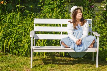 Cute little girl in a hat sitting on a garden bench