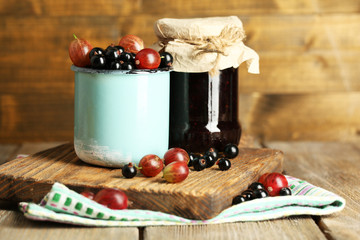 Ripe blackcurrants and gooseberries in mug and glass jar with