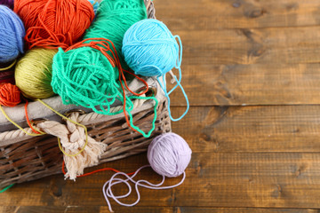 Multicoloured knitting yarn in basket on wooden background