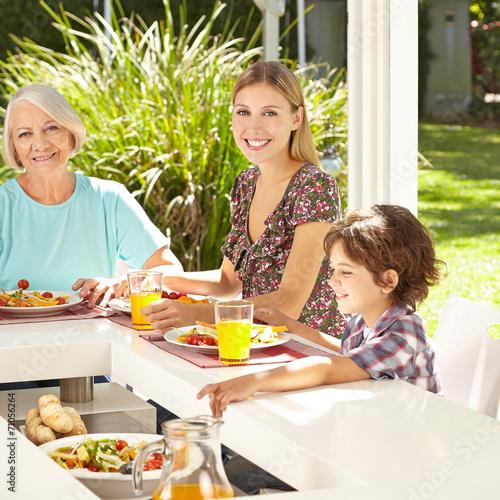canvas print picture Kind beim Essen mit Mutter und Großmutter