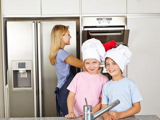Zwei Kinder mit Mutter in der Küche