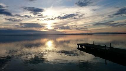 Puesta de sol en lago con muelle