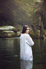 Beautiful woman posing in a mountain stream
