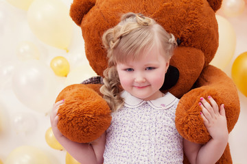 Cute little girl in arms of large teddy bear