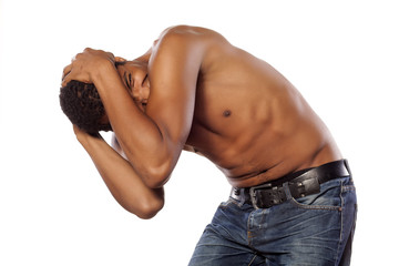 frightened half-naked young african man in self-defense position