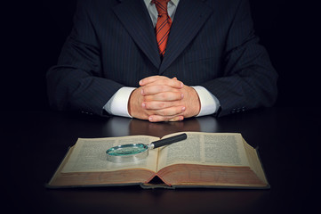 Businessman with old book and magnifying glass