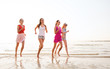 canvas print picture - group of smiling women running on beach