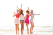 group of smiling women dancing on beach