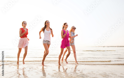 canvas print picture group of smiling women running on beach