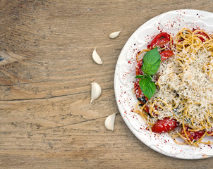 A plate of tomato and basil pasta on a wooden desk