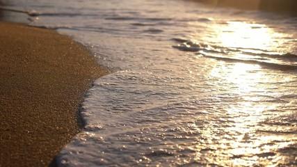Closeup Calm Sea Waves on Sandy Beach at Sunset. Slow Motion.