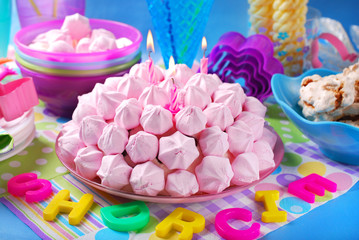 birthday cake with pink meringues and candles