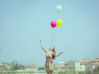 girl releasing balloon in the sky