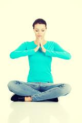 Student girl meditating in lotus pose.