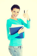 Portrait of a beautiful young woman student gesturing ok.