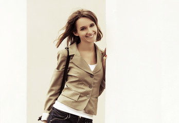 Happy young fashion woman at the wall