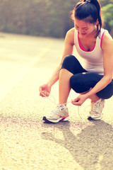 woman runner tying shoelace on country road