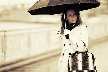 Beautiful fashion woman with umbrella walking on the city street
