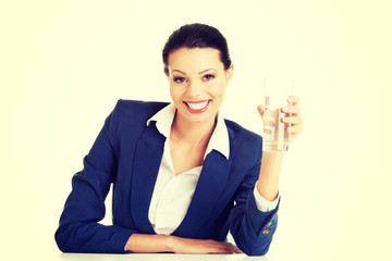 Businesswoman sitting at the desk with mineral water