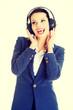 Happy attractive businesswoman listening the music through headp
