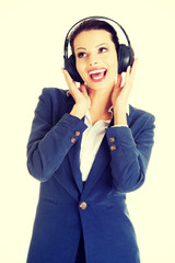 Happy attractive businesswoman listening the music through headp