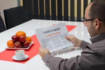 Man reading cyber attacks article in the newspaper