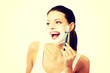 Beautiful young woman shaving her face