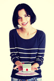 Happy woman holding euros bills and house model