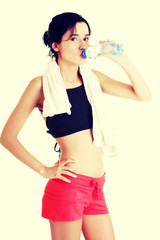 Young fit woman drinking mineral water