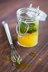 Salad dressing with olive oil chili and herbs in a glass jar