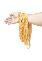 a group of golden necklace in human arm isolated on white