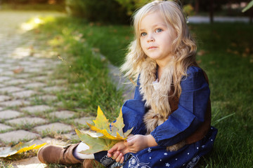 Adorable little girl with autumn leaves in park