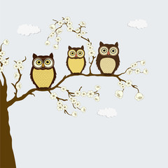 Cute family of owls on a branch with flowers