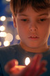 Boy with burning candle in a hand frontal view
