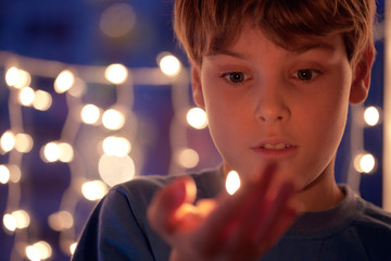 boy with astonishment looks at a burning candle in a hand