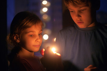 girl and boy look at a burning candle