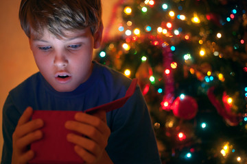 Boy with surprise looks a New Year gift