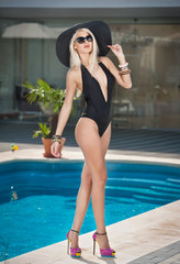 Beautiful sensual blonde with fashionable sunglasses and hat
