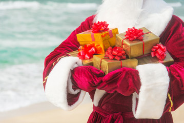 Santa Claus close up with many golden gifts on sea beach